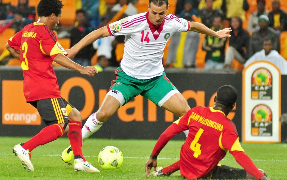 Difensori dell'Angola contrastano calciatore marocchino durante un match del 2013